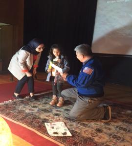 Daniel Tani avec un enfant marocain lui donnant un dessin de l'espace